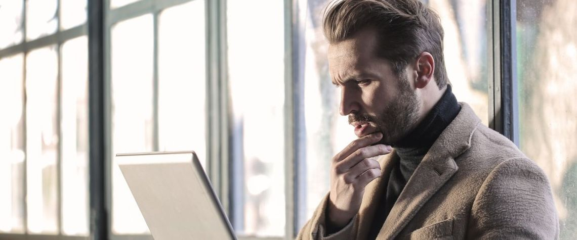 man looking at laptop considering his medicare options and the best medicare supplement