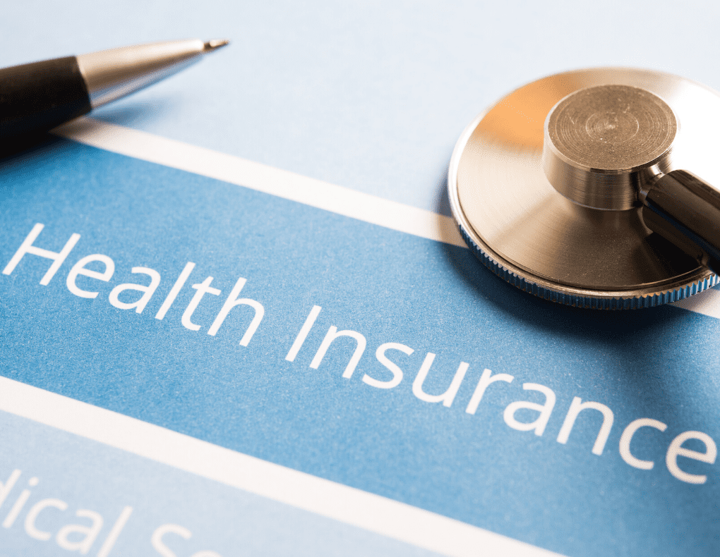 health insurance printed on paper with pen and stethoscope on top